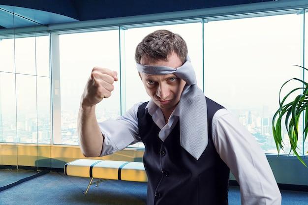 Злой бизнесмен с галстуком на голове в офисе