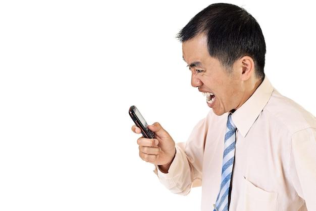 白い壁に携帯電話で怒っている実業家。