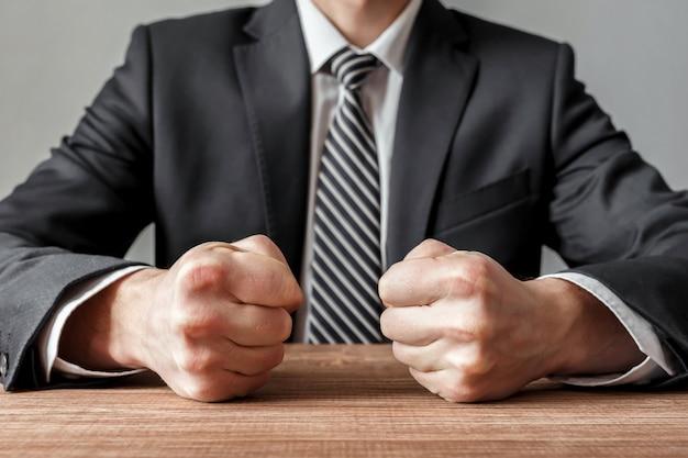 テーブルの上に閉じた拳で怒っているビジネスマン