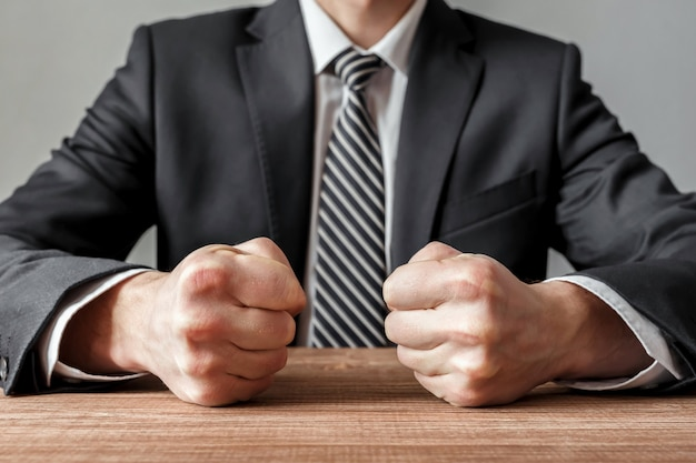 Angry businessman with closed fists on the table