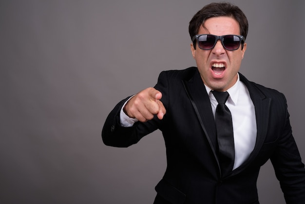 Angry businessman with sunglasses pointing at camera