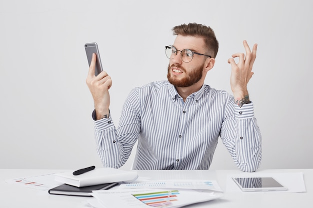 Angry businessman with trendy hairstyle, wears round spectacles, looks furiously into cell phone