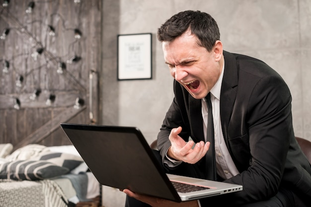 Angry businessman yelling at laptop at home