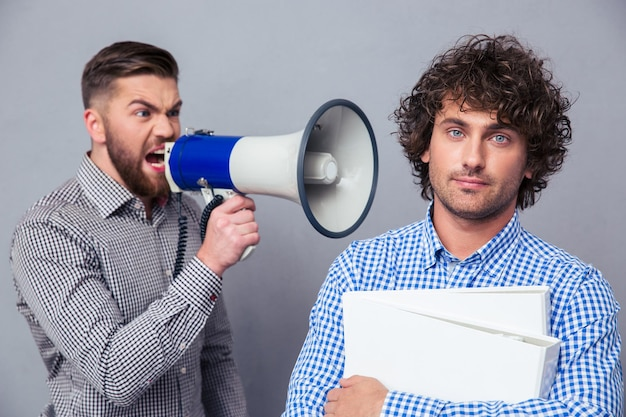 Angry businessman yelling via megaphone to another man over gray wall