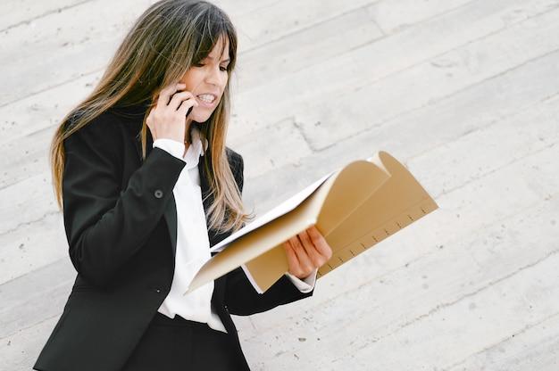 Сердитая деловая женщина держит документы и кричит по телефону