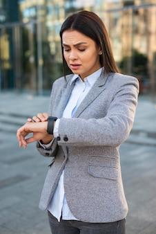 屋外で彼女の時計を見ている怒っている実業家
