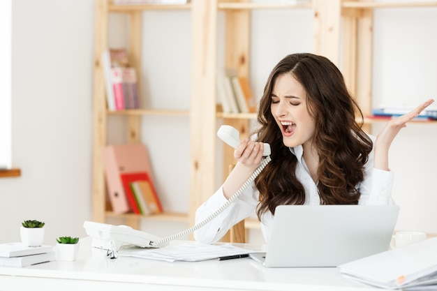 Angry businesswoman shouting on phone in modern office