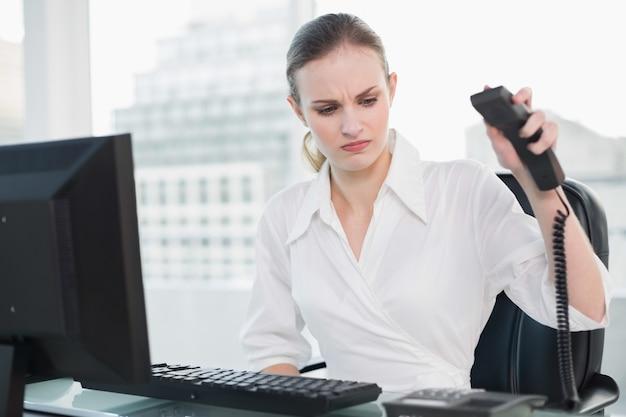 電話を掛けている机に座っている怒っている実業家