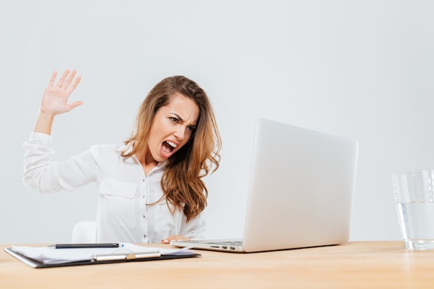 Angry businesswoman sitting at the table and screaming at laptop in office over white background