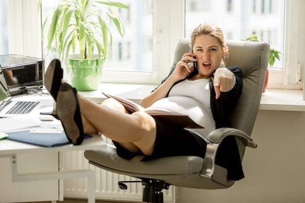 Сердитая деловая женщина разговаривает по телефону, кричит и указывая рукой