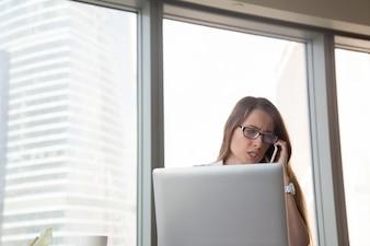 セルで主張し、職場で携帯電話で話している怒っている実業家