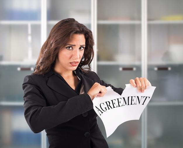 Сердитая деловая женщина разрывает договор листового документа