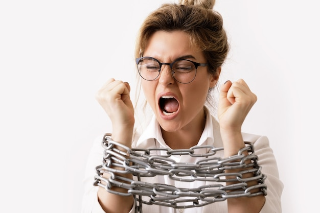 Angry businesswoman tied up with a chains is screaming