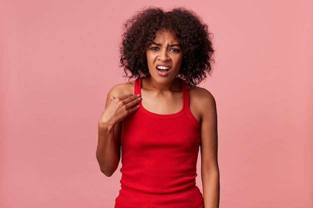 不当な主張に腹を立てているアフリカ系アメリカ人の男性は、巻き毛の黒い髪の赤いtシャツを着ています。ピンクの背景の上に隔離されたカメラを眉をひそめ、見ながら、左手で自分自身を指しています。