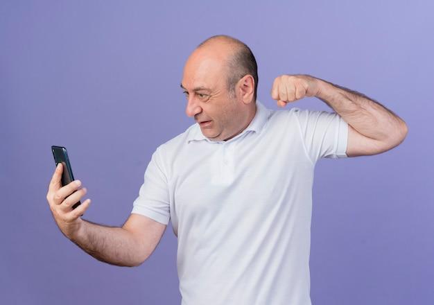 화가 캐주얼 성숙한 사업가 들고 휴대 전화를보고 보라색 배경에 고립 된 주먹을 올리는