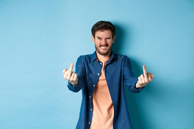 怒っている白人男性は、あなたを性交し、中指を見せて、怒り狂った顔で失礼なジェスチャーをし、青い背景にイライラして立っていると言います。