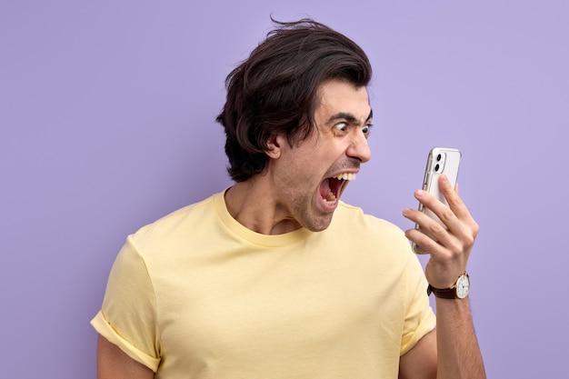 휴대 전화의 화면을보고 스마트 폰에서 비명 화가 백인 남자
