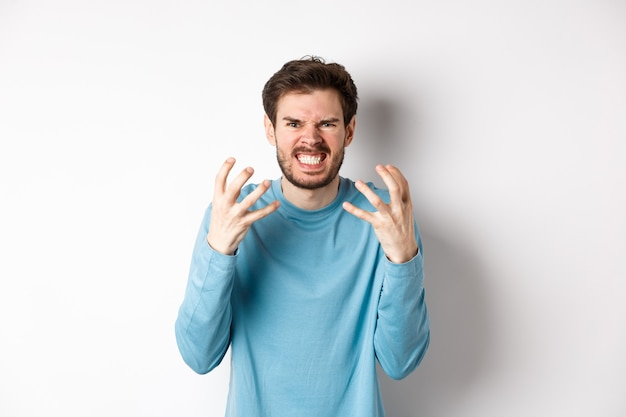 Angry caucasian man shaking hands and grimacing, looking with mad face, express hatred against white background