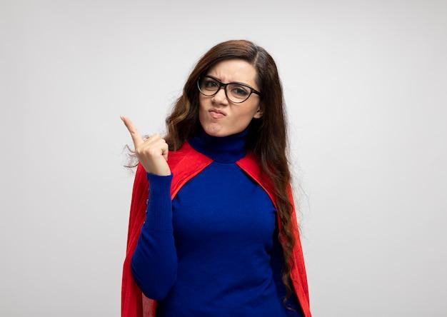 光学メガネの赤いマントを持つ怒っている白人のスーパーヒーローの女の子は、コピースペースで白い壁に人差し指を分離します