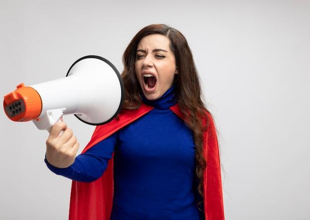 赤いマントの怒っている白人のスーパーヒーローの女の子は、コピースペースのある白い壁に隔離されたラウドスピーカーに見えて叫びます