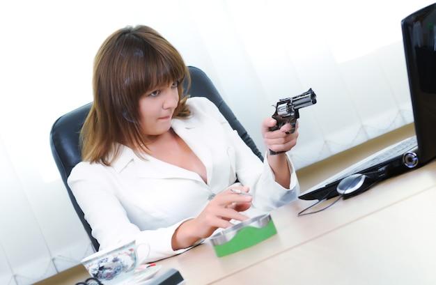화난 백인 백인 갈색 머리 여자는 노트북 화면에서 권총을 목표로 합니다. 불만을 품은 여성 회사원이나 담배를 손에 들고 있는 사업가. 책상에 재떨이입니다. 밝은 배경