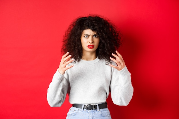 怒って手を上げて眉をひそめている怒っている白人女性は、迷惑なスタンを絞め殺したり殺したりしたいと思っています...