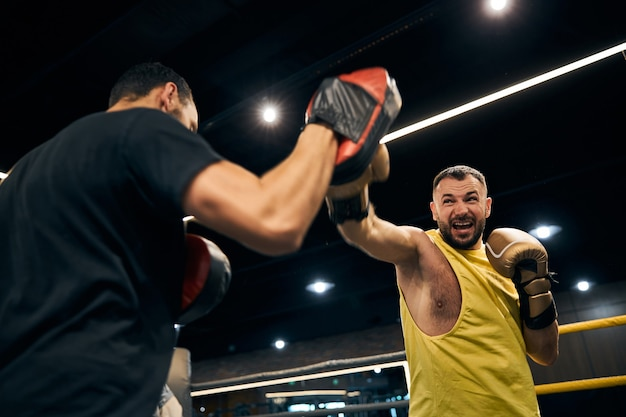 Angry champion attacking a boxing focus pad on the hand of his coach