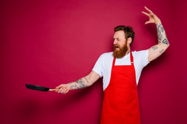 Angry chef with beard and red apron cooks with pan