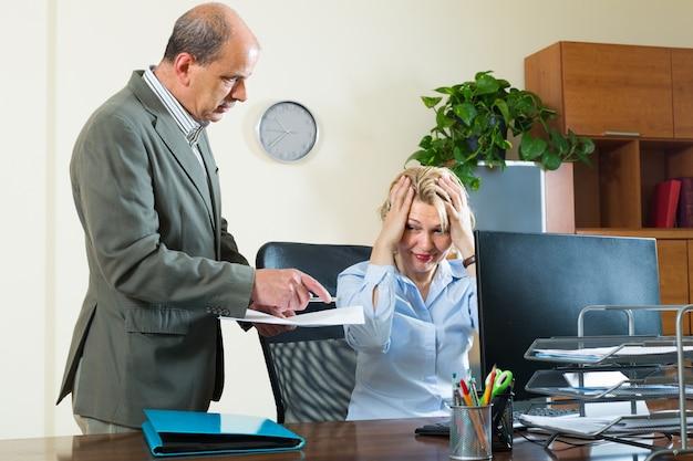 Сердитый начальник и секретарь в офисе