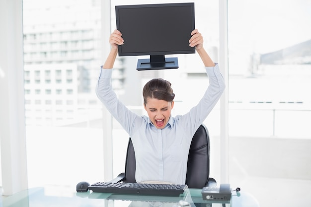 Angry classy brown haired businesswoman throwing her computer screen