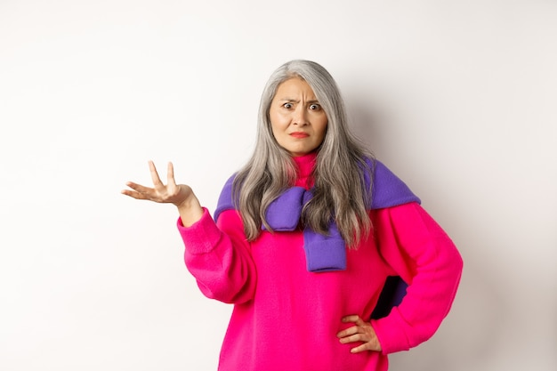 Angry and confused asian senior woman spread hand sideways and staring at camera puzzled, standing in pink sweater against white background