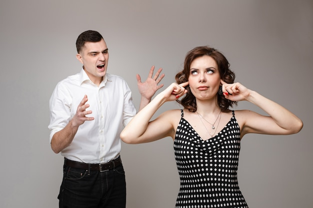 Angry couple in love stands and screams to each other, picture isolated on grey wall