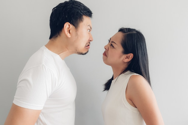 Angry couple lover in white t-shirt and grey background.