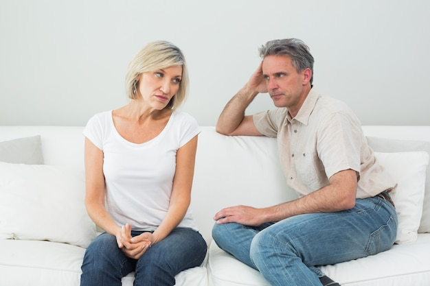 Angry couple sitting on sofa after a fight