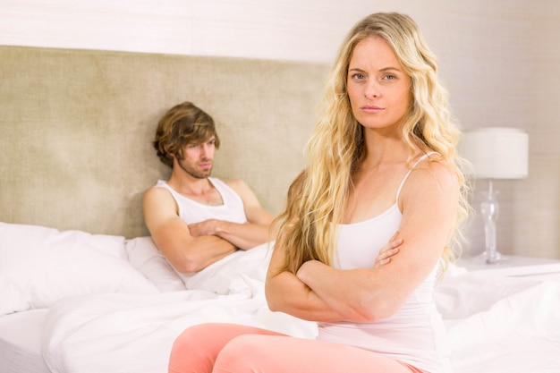 Angry couple sulking each other in the bedroom