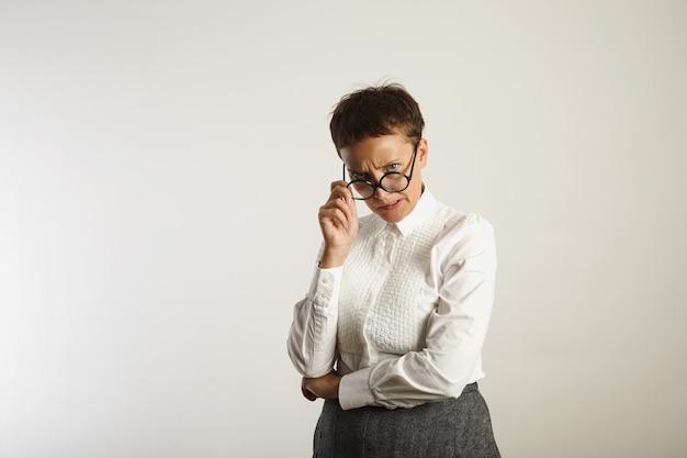 白い壁に彼女の丸い黒い眼鏡を調整する怒っている狂ったように見える先生