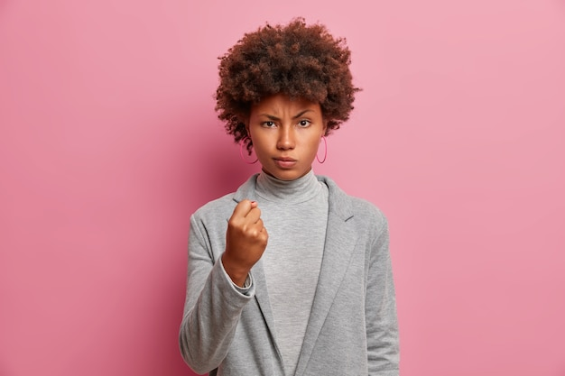怒っている縮れ毛の実業家は彼女の攻撃性を示し、くいしばられた握りこぶしを上げ、顔を眉をひそめ、人を脅かし、灰色の服を着て、深刻な失礼な表情をしています