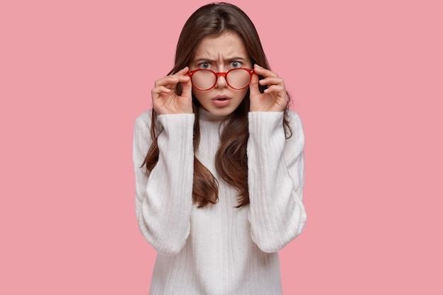 La donna arrabbiata dai capelli scuri ha esaminato attentamente lo sguardo attraverso gli occhiali, insoddisfatta di qualcosa, indossa un maglione bianco casual