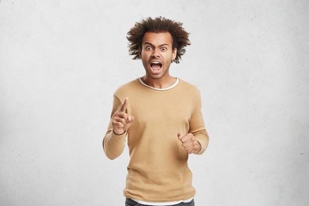 화난 어두운 피부의 남성이 누군가를 비난하고 큰 소리로 비명을 지르며 외칩니다.