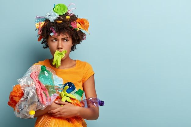 화난 어두운 피부를 가진 여성은 입에 고무 장갑을 끼고 얼굴을 능글 맞이하며 플라스틱 오염에 반대합니다.