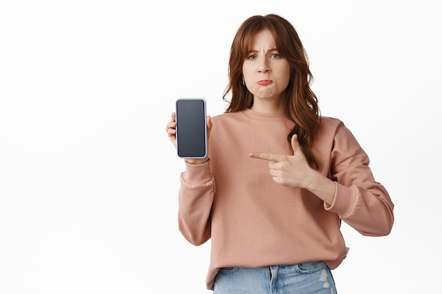 Angry and disappointed girl pointing finger at smartphone screen, complaining on something posted online, bad app or photo, standing upset on white