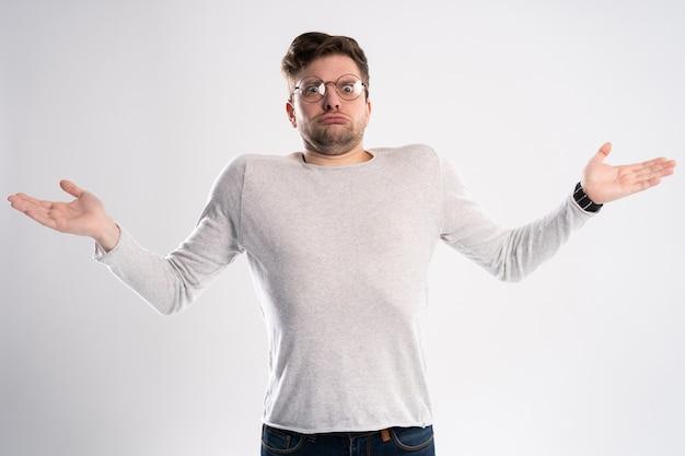 Сердитый разочарованный мужчина возмущенно развел руками, неуверенно смотрит, носит оптические очки