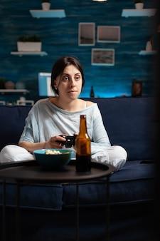 テレビでサッカーのビデオゲームをプレイするゲームのジョイスティックを持っている怒っている失望した女性は、オンラインビデオゲームの競争に負けています。深夜にリラックスしてパジャマを着て欲求不満の表情豊かな人