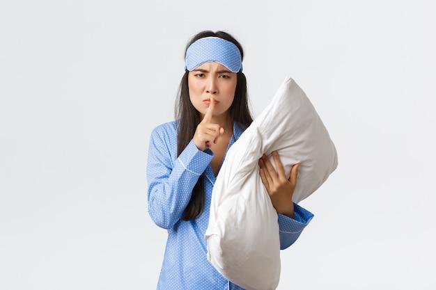 Сердитая недовольная азиатская девушка в спальной маске и пижаме, держащая подушку и хмурясь, встревоженная, шипит, говорит, что просыпается от громкого шума, просит людей молчать ночью, белый фон.