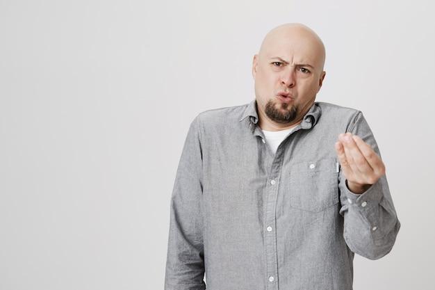 怒って不機嫌なハゲ男が判断または不平を言う