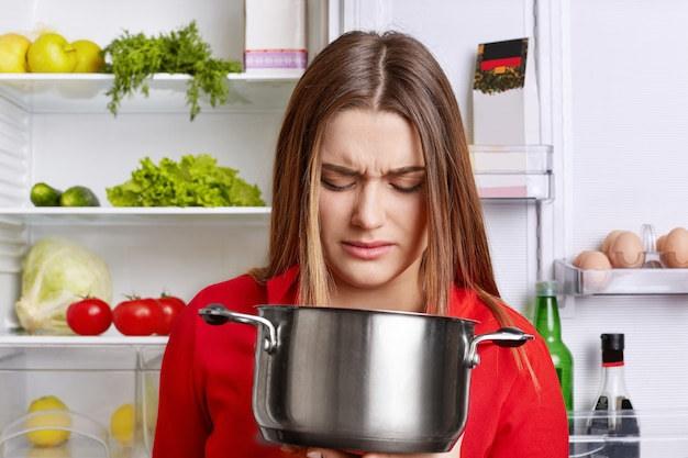 Angry displeased female housewife looks in pot with foul meal, smells unpleasant stink, stands near fridge with fresh fruit and vegetables, going to cook supper.