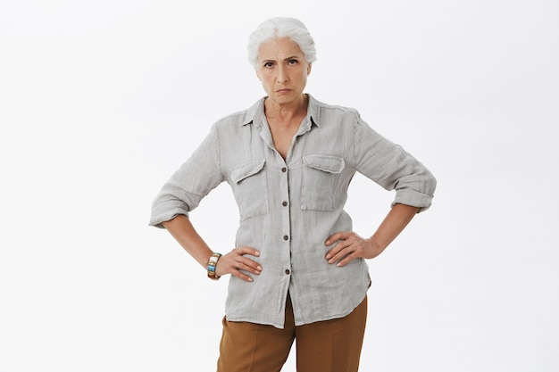Злая недовольная бабушка, хмурясь и держась за руки за талию, ругает детей