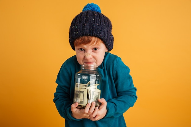 Angry displeased little redhead boy holding jar with money.