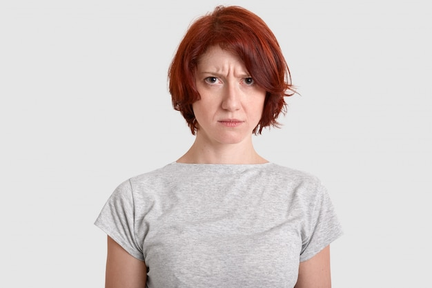 Angry displeased woman with red hair, expresses negative feelings, frowns face in displeasure, wears casual t shirt, isolated over white wall, looks in discontent. people and emotions concept