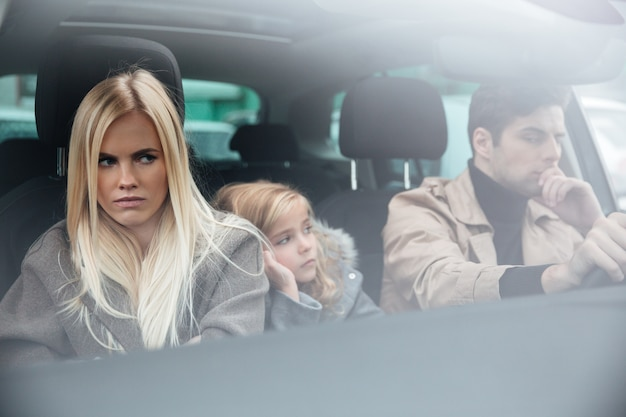 Angry displeased young family sitting in car after quarrel